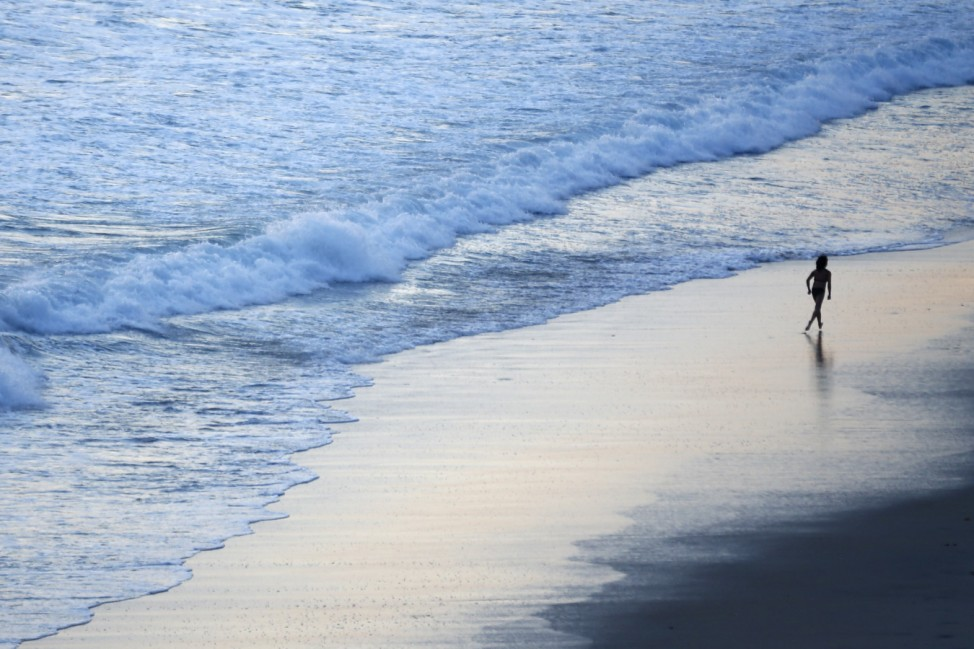 A young girl runs along the beach after sunset in Leicadia