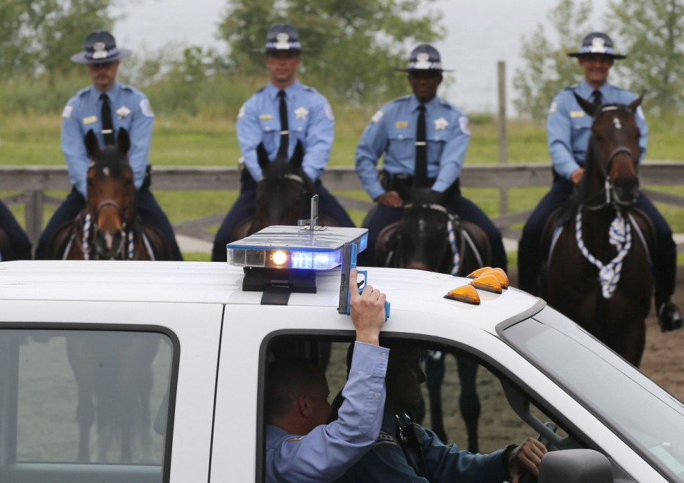 A Chicago police officer uses a gun to fire blanks as he drives around the Department's Mounted Patrol Unit graduating class to display the stability in the training of the horses in Chicago