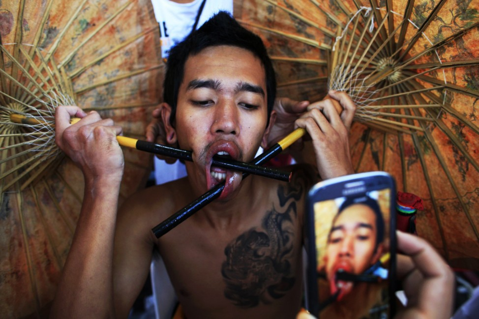 A devotee of the Chinese Bang Neow Shrine with pierced umbrellas through his cheeks waits for a street procession during the annual vegetarian festival in Phuket