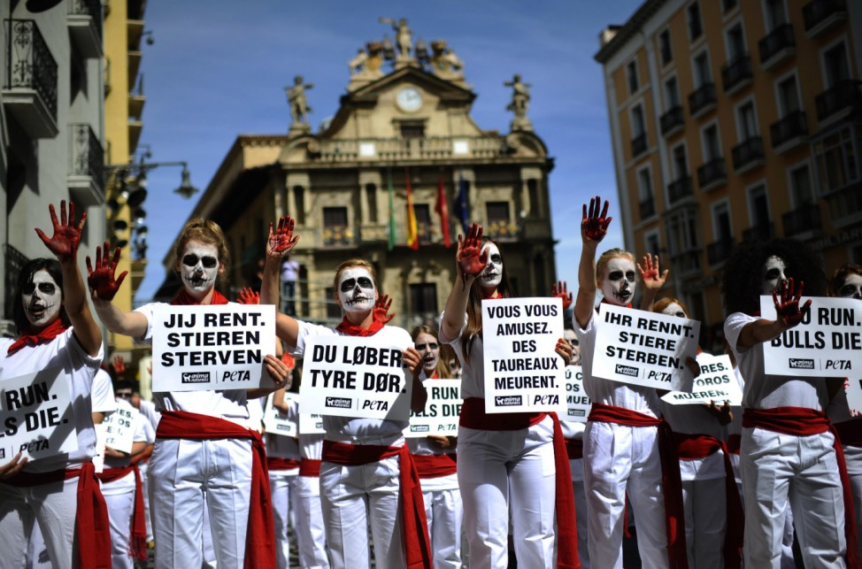Anti-bullfighting protesters wearing skull make-up and traditional red scarves hold up signs that read, 'You Run. Bulls Die', during a demonstration in front of Pamplona town hall