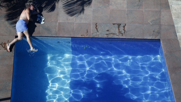Man lies by a hotel swimming pool during the 2014 World Cup in Manaus