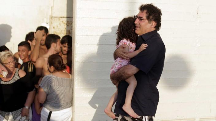 Alltag im Nahostkonflikt: Nahostkonflikt: Ein Israeli trägt sein Kind in einen Luftschutzbunker in Tel Aviv.