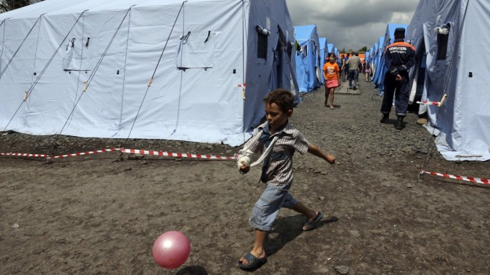 A boy plays with a ball at a temporary tent camp set up for Ukrainian refugees in the town of Novoshakhtinsk