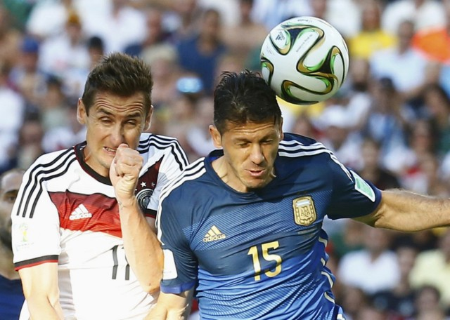 Argentina's Demichelis heads the ball beside Germany's Klose during their 2014 World Cup final at the Maracana stadium in Rio de Janeiro