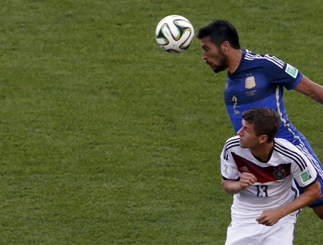 Argentina's Garay heads the ball past Germany's Mueller during their 2014 World Cup final at the Maracana stadium in Rio de Janeiro