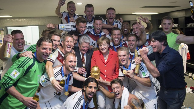 German Chancellor Merkel and German President Gauck pose with the Germany's coach Loew and his players after Germany beat Argentina in the 2014 World Cup final at the Maracana stadium in Rio de Janeiro