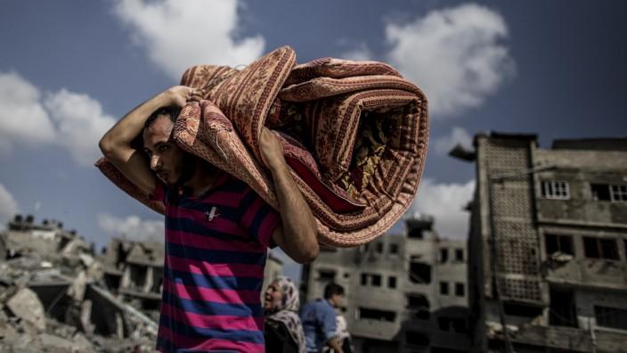 Gazastreifen: Ein Palästinenser nutzt eine kurze Feuerpause, um Zuflucht zu finden.