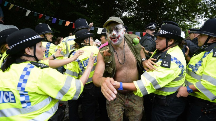 Police scuffle with a demonstrator outside a drill site run by Cuadrilla Resources, near Balcombe in southern England