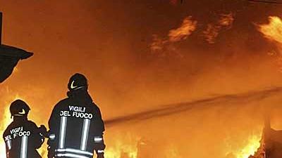 Italien: Eine Aufnahme, die nahe Neapel entstand: Feuerwehrleute versuchen eine angezündete Roma-Siedlung zu löschen.