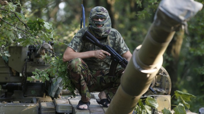 Pro-Russian separatist from the Vostok battalion poses for a picture atop a T-64 tank in Donetsk, eastern Ukraine