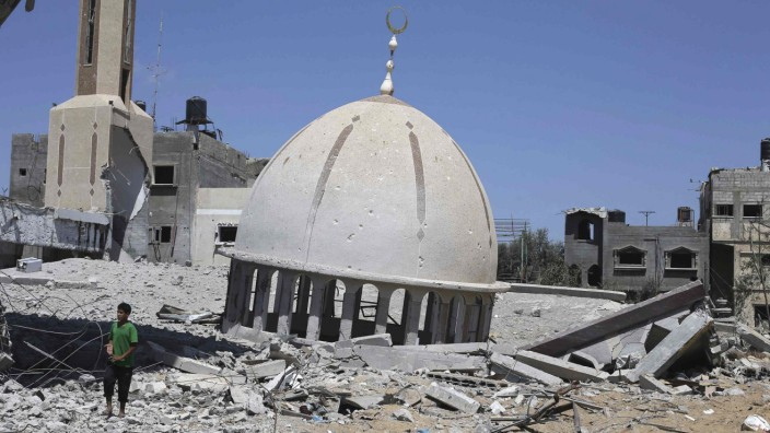Palestinian boy stands next to the remains of a mosque in Khuzaa town in the southern Gaza Strip