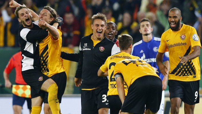 Dynamo Dresden players celebrate after they defeated Schalke 04 during their German soccer cup match in Dresden