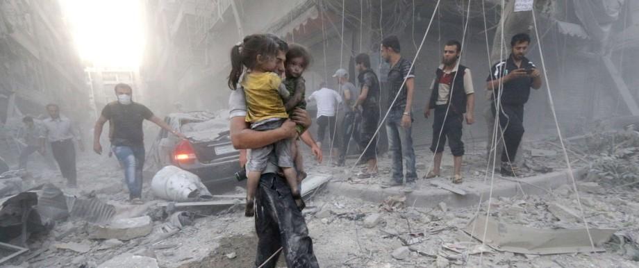 Syrien: Ein Mann trägt zwei Mädchen nach einem Luftschlag der Regierungstruppen in der syrischen Stadt Aleppo (Archivbild vom Juli 2014).