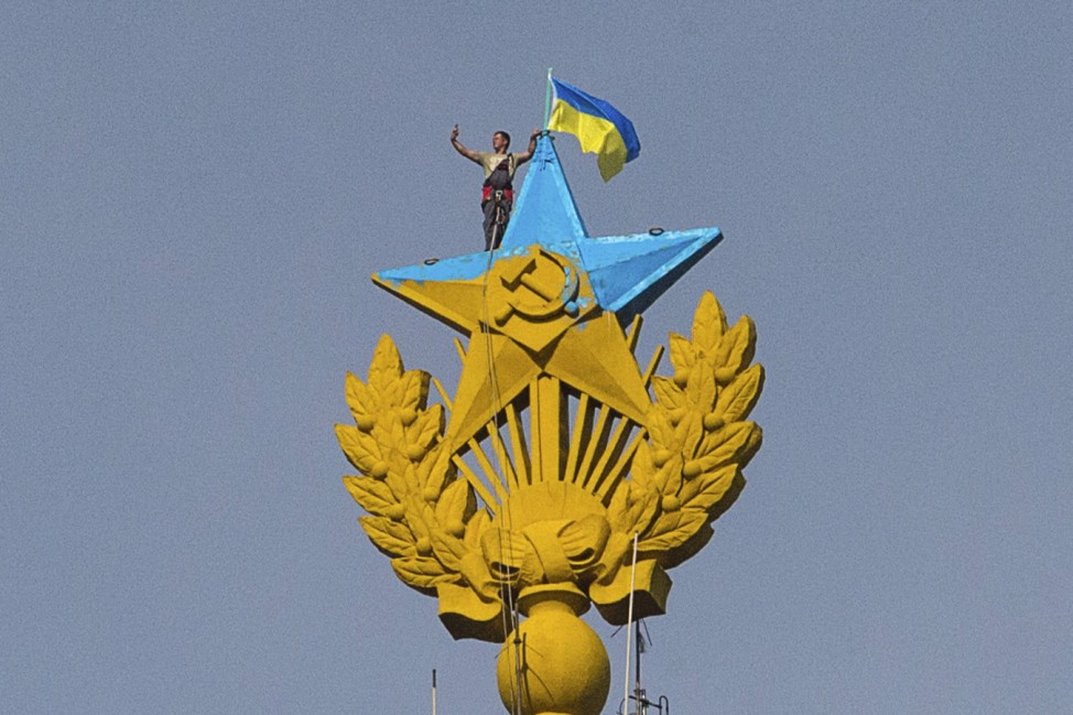 A man takes a 'selfie' as he stands with a Ukrainian flag on a Soviet-style star re-touched with blue paint so it resembles the yellow-and-blue national colours of Ukraine, atop the spire of a building in Moscow