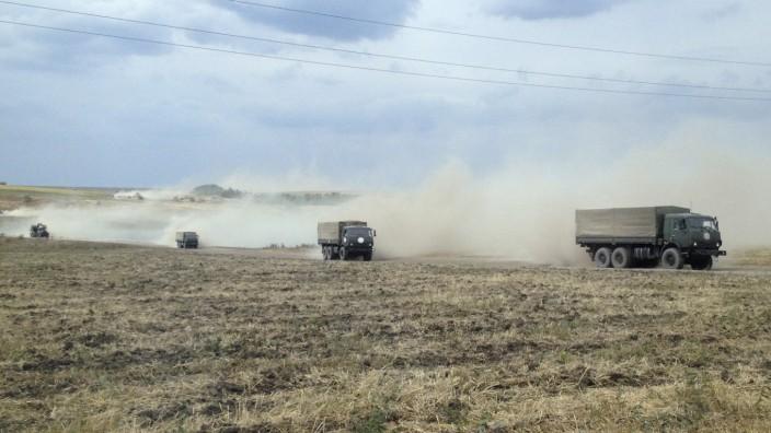 Military trucks travel through the steppe near the village of Krasnodarovka