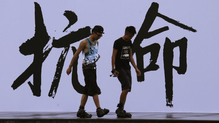 Pro-democracy activists walk past a backdrop with Chinese characters that read 'disobedience' in Hong Kong