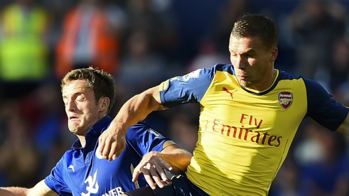 Leicester City's King challenges Arsenal's Podolski during their English Premier League soccer match at the King Power Stadium in Leicester