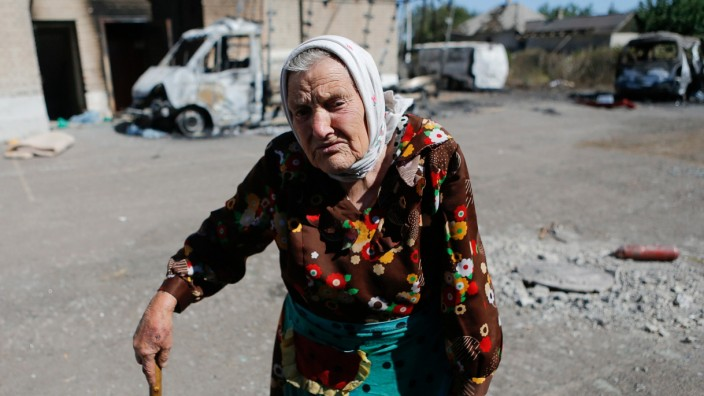 A woman stands in front of vehicles destroyed during recent shelling in the eastern Ukrainian town of Ilovaysk