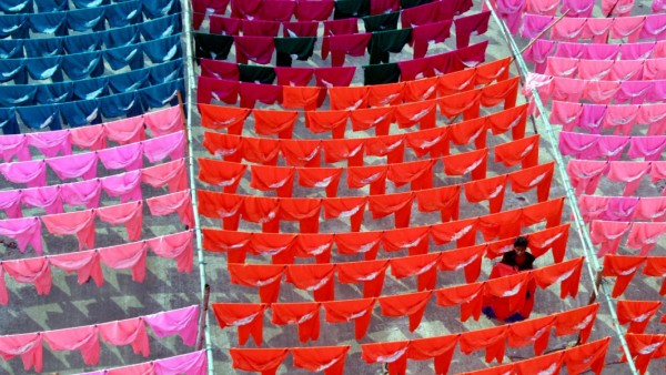 File photo of a worker hanging clothes to dry on the roof of a garment factory in Dhaka