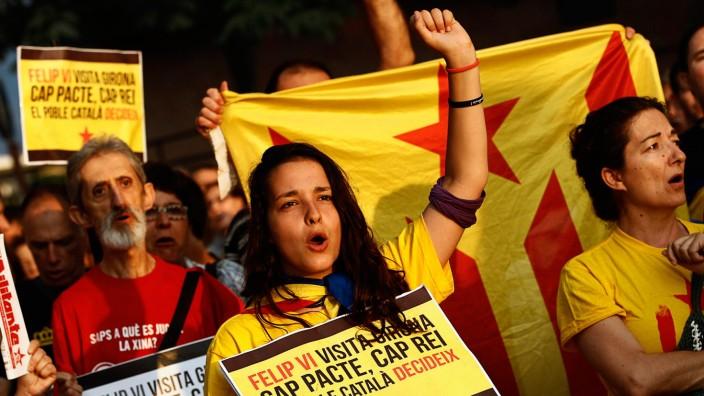 """Spanien: Pro-Unabhängigkeits-Demonstration in Girona: """"Das katalanische Volk entscheidet"""" steht auf dem Plakat der jungen Frau, die gegen den Besuch des spanischen Königs protestiert."""