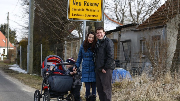 Pawel Pilsniak, his wife Anna and two children Micheasz and Nathan pose for a photograph by the entrance to the village of Neu Rosow