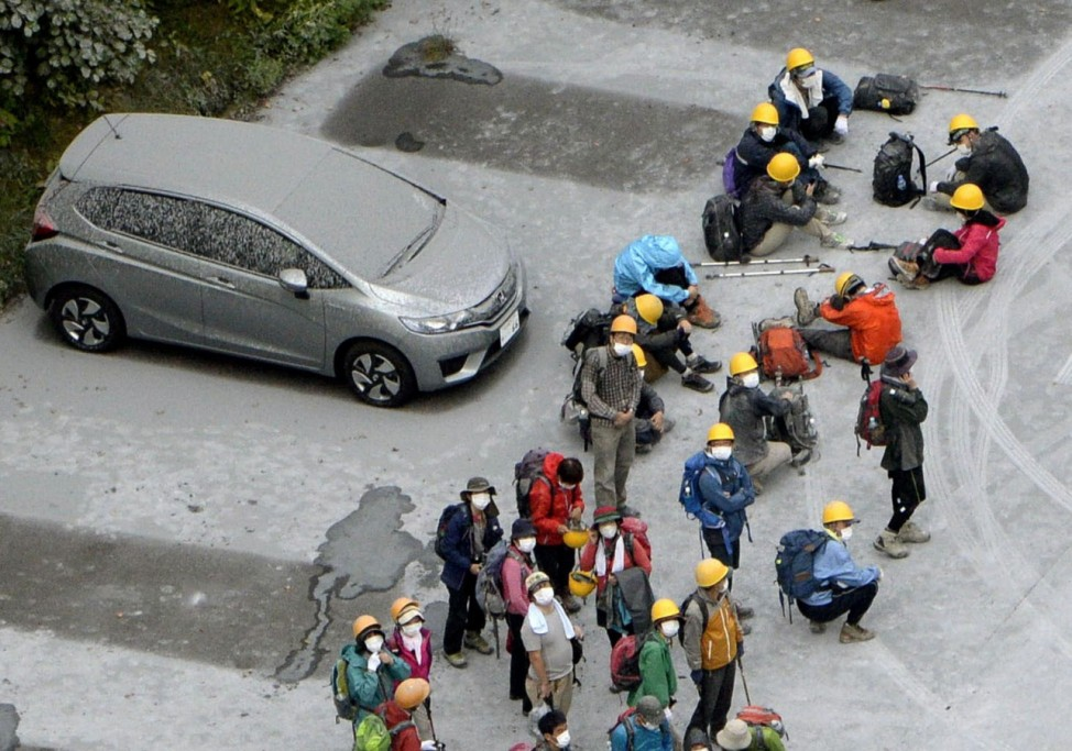 Climbers and a car, covered with volcanic ash, are seen at a parking near Mount Ontake in Kiso town in Nagano prefecture