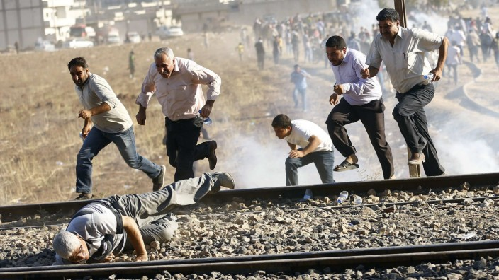 Turkish and Syrian Kurds run as Turkish security forces use tear gas to disperse them near the Mursitpinar border crossing on the Turkish-Syrian border, near Suruc