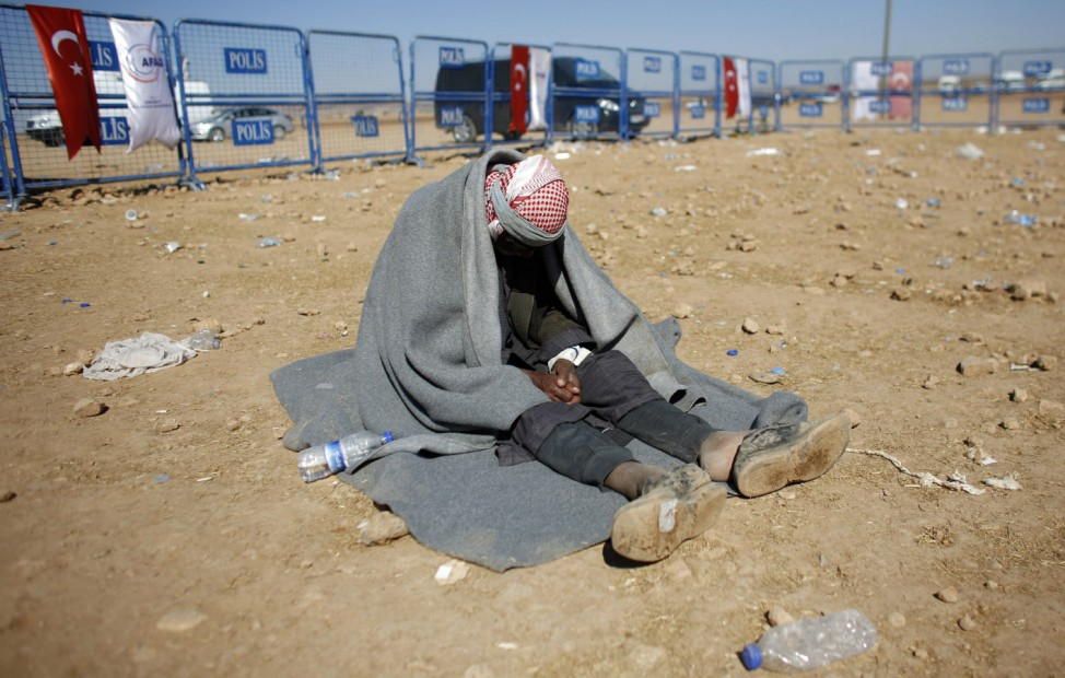 Mohammad Osman, a 100-year old Syrian Kurdish refugee man, waits for transportation after crossing into Turkey near the southeastern Turkish town of Suruc in Sanliurfa province