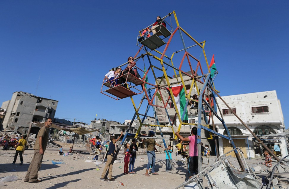 Palestinian children play on a swing on the first day of the Muslim Eid al-Adha holiday in Beit Hanoun town in the northern Gaza Strip