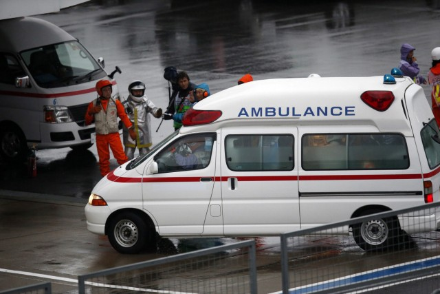Marshalls clear the way for an ambulance after the race was stopped following a crash by Marussia Formula One driver Bianchi of France at the Japanese F1 Grand Prix at the Suzuka Circuit