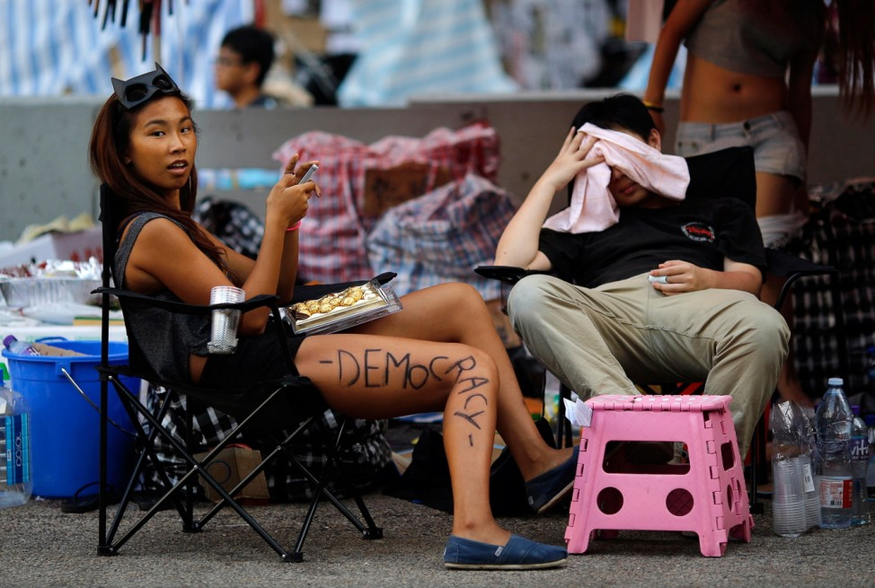 Protester sits under a tent as she helps to block an area around the government headquarters in Hong Kong