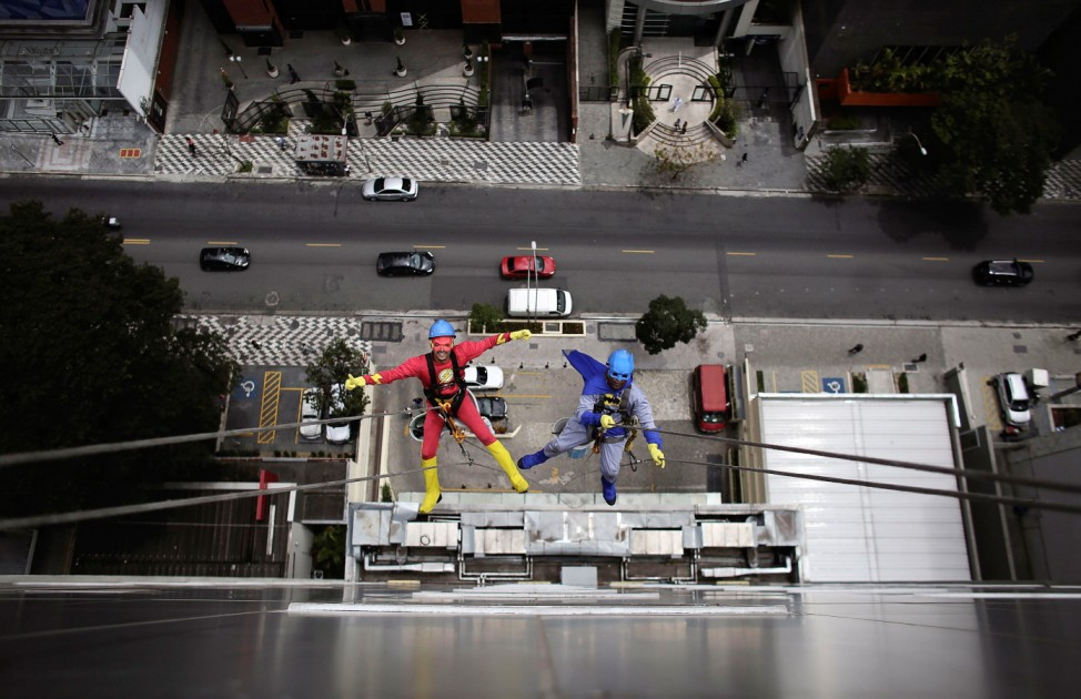 Men dressed as Batman and Flash prepare to clean the glass facade of Hospital Infantil Sabara before meeting with patients of the children's hospital in Sao Paulo
