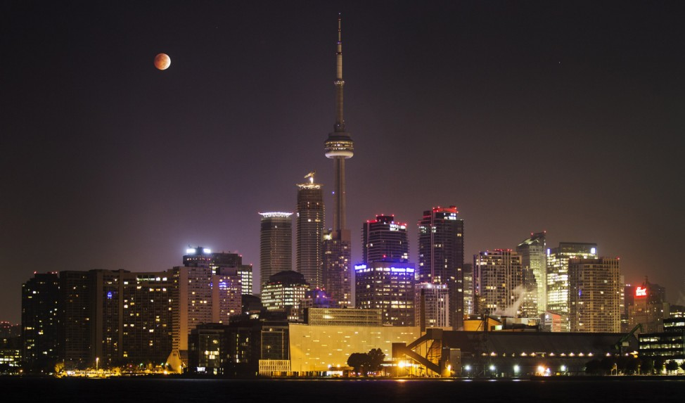 The moon turns orange during a total lunar eclipse behind the CN Tower and the skyline during moonset in Toronto