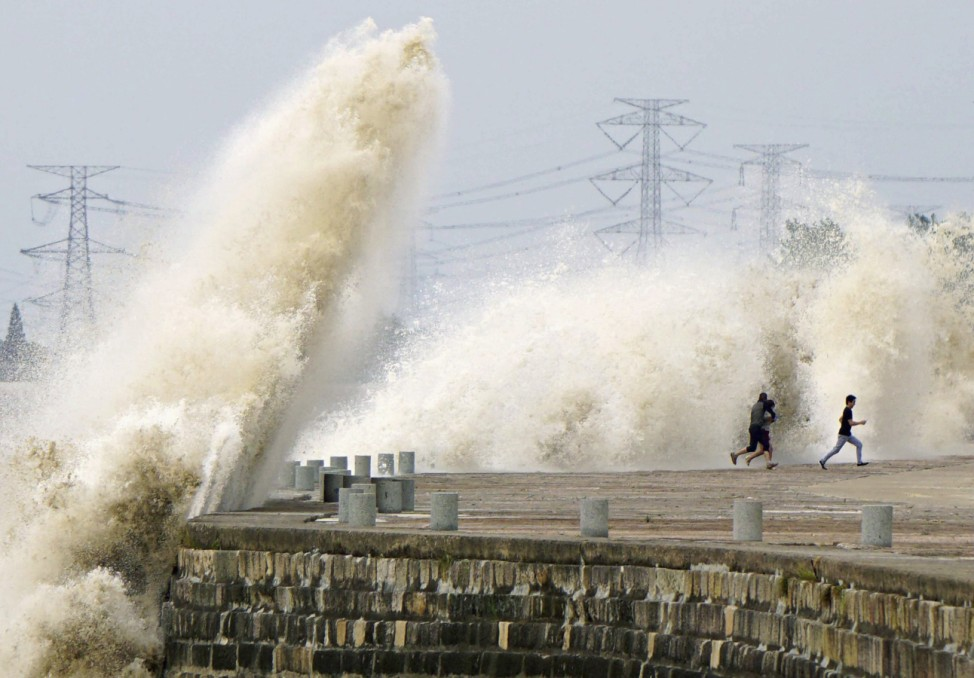 People run away from waves caused by a tidal bore which surged past a barrier on the banks of Qiantang River, in Haining