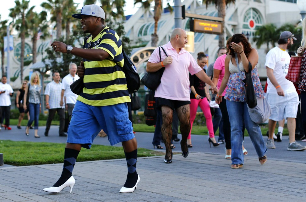 Men and women walk through downtown wearing high heel shoes as part of an event called 'Walk a Mile in Her Shoes' to help raise awareness of domestic violence in San Diego