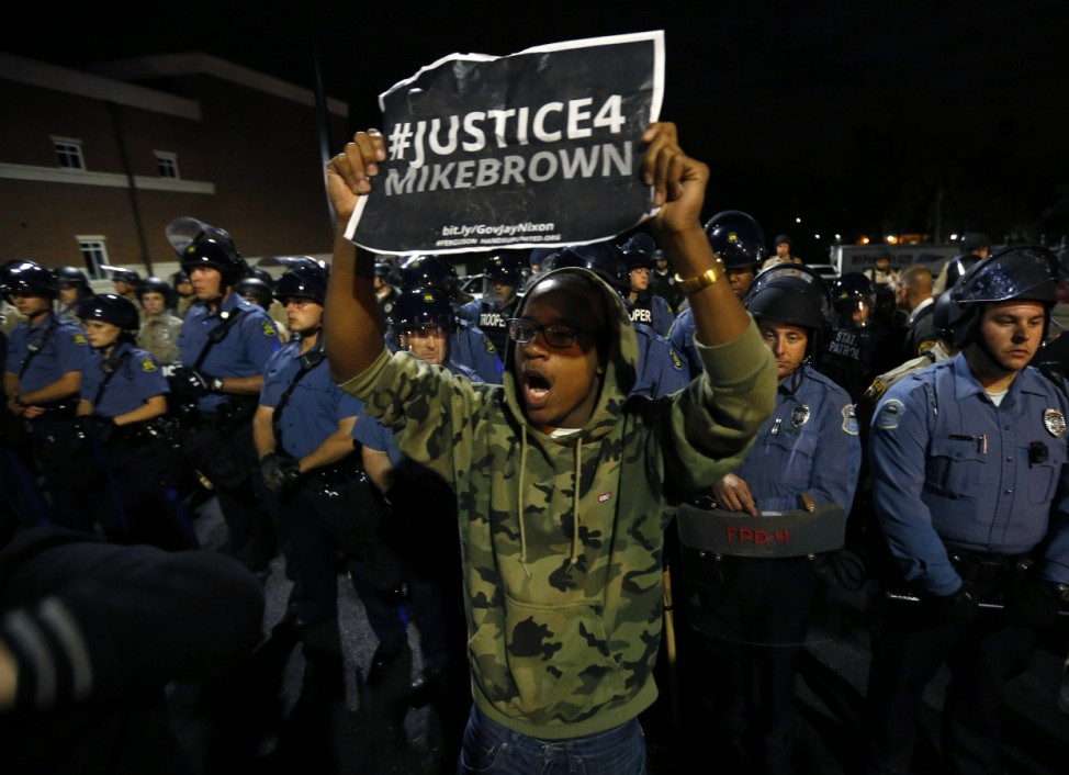 A protester demonstrates in front of a police line in Ferguson