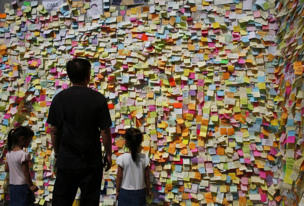 Man and girls read messages left by pro-democracy protesters outside the government headquarters in Hong Kong