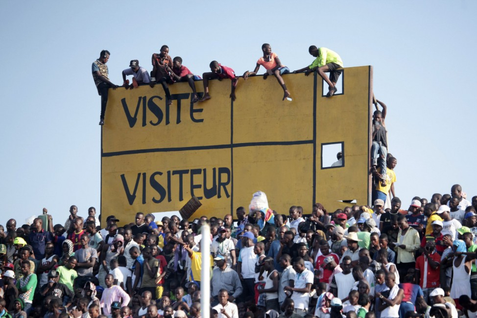 Fans climb a scoreboard to watch the African Cup of Nations qualifying match between Ivory Coast and Democratic Republic of Congo in Kinshasa