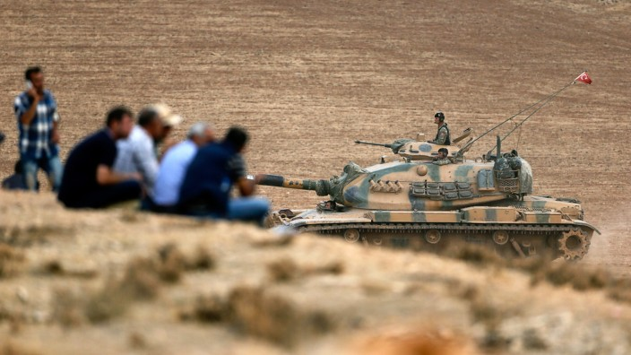 A Turkish army tank manoeuvers as Turkish Kurds watch over the Syrian town of Kobani from atop a hill near Mursitpinar border crossing in the southeastern Turkish town of Suruc