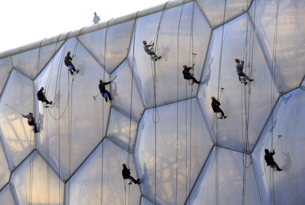Workers clean the exterior of the National Aquatics Centre, also known as the 'Water Cube', in Beijing