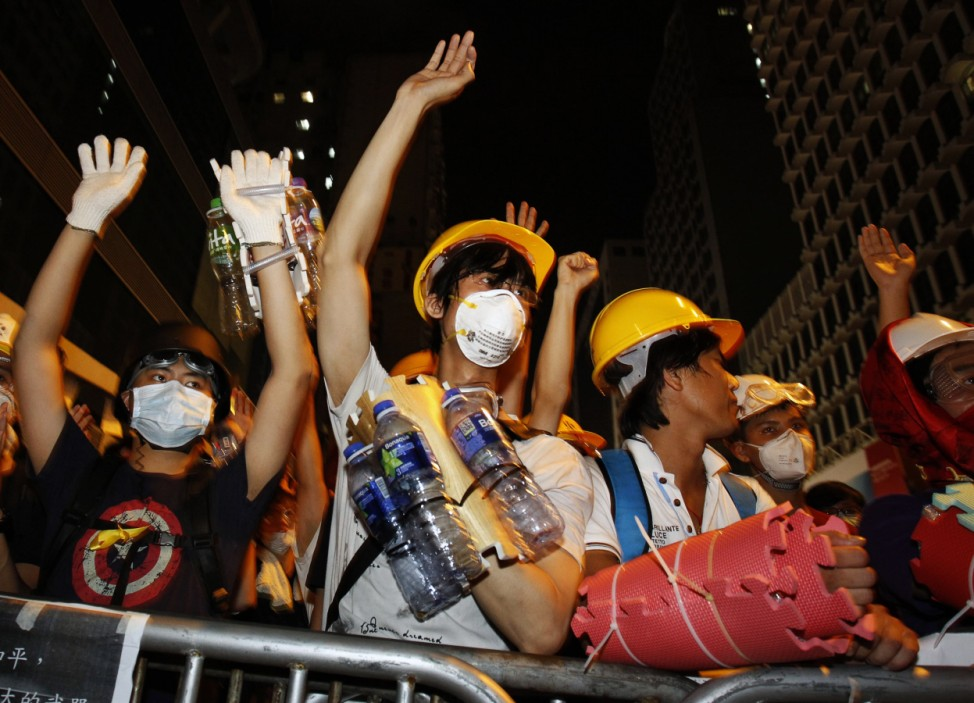 Pro-democracy protesters raise their hands at riot police as a gesture of peace after they were told not to charge the police defence line, in Mongkok