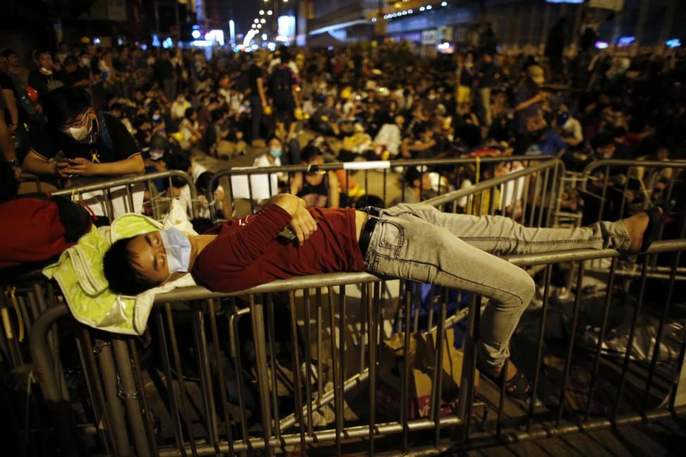 Pro-democracy protester sleeps over a barricade at the Mongkok shopping district of Hong Kong
