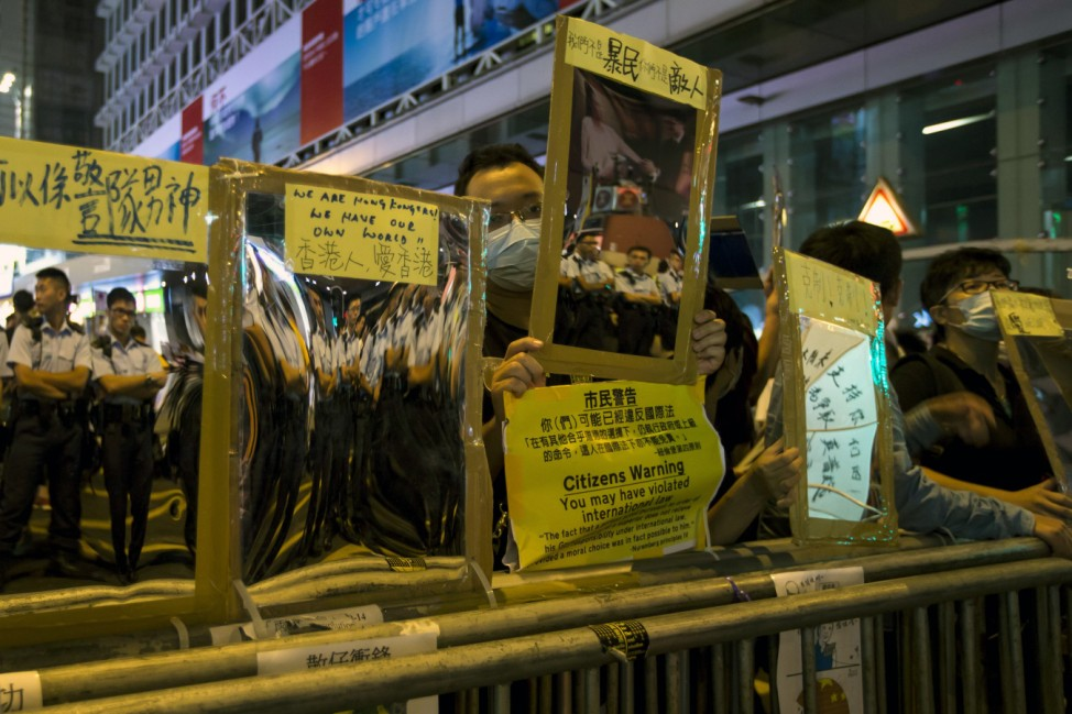 Police officers are reflected on reflective materials held by a pro-democracy protesters on a blocked road at Mongkok shopping district in Hong Kong