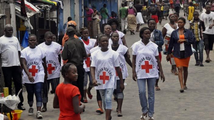 Ebola-Hilfe: Rot-Kreuz-Mitarbeiter laufen durch einen Slum der liberianischen Hauptstadt Monrovia, in dem Ebola ausgebrochen ist.
