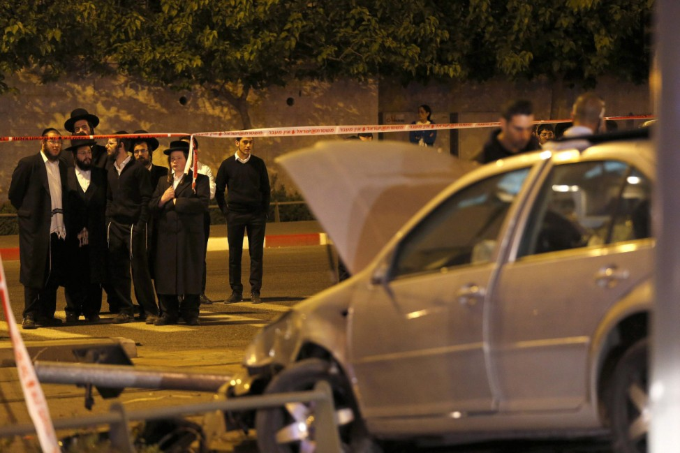 Israelis stand behind a police barrier next to a car wreck in Jerusalem