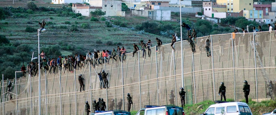 African migrants sit atop a border fence between Morocco and Melilla during an attempt to cross into Spanish territory