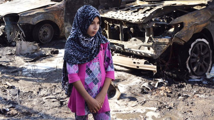 A girl walks past the site of a car bomb attack in Baghdad