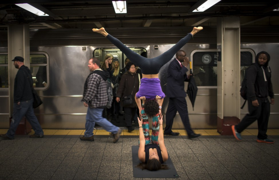 Lauren Pallody and Bassam Kubba practice 'Acro-yoga' a mixture of yoga and acrobatics on a subway platform at 42nd Street beneath Grand Central station in New York city