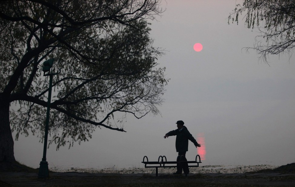A man does his morning exercise on a polluted day by the side of a lake at Nanhu Park in Changchun