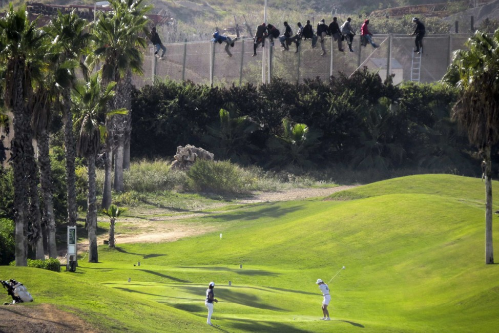A golfer hits a tee shot as African migrants sit atop a border fence during an attempt to cross into Spanish territories between Morocco and Spain's north African enclave of Melilla